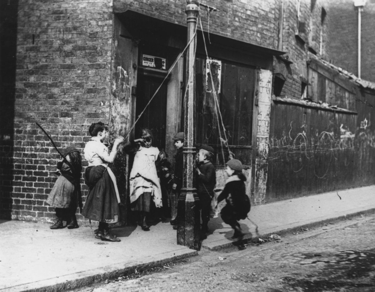 Circa 1892: Children living in the slums improvise a lamppost and some rope as a swing. (Photo by Paul Martin/Getty Images)